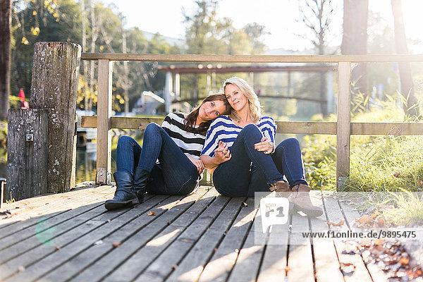 Verliebtes Lesbenpaar auf einem Steg sitzend