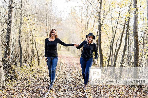 Zwei Frauen balancieren auf Schienen