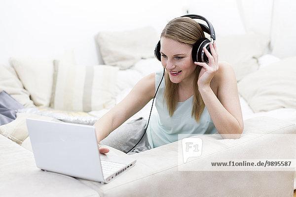 Porträt einer Frau auf einer Couch mit Kopfhörer und Laptop