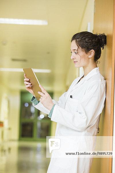 Junger Arzt mit digitalem Tablett auf dem Krankenhausboden