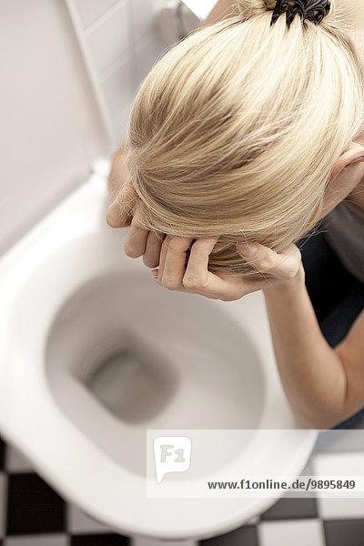 Verzweifelte magersüchtige junge Frau auf der Toilette