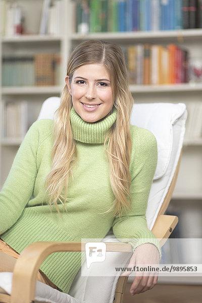 Lächelnde junge Frau im Sessel sitzend