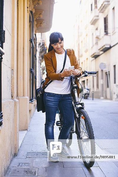 Spanien  Barcelona  lächelnde Frau mit Fahrrad und Handy in der Stadt