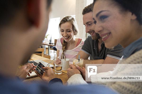 Gruppe glücklicher Freunde mit Laptop und Smartphone