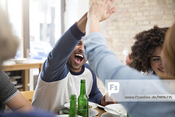 Glückliche Freunde am Esstisch mit Bierflaschen High Fiving