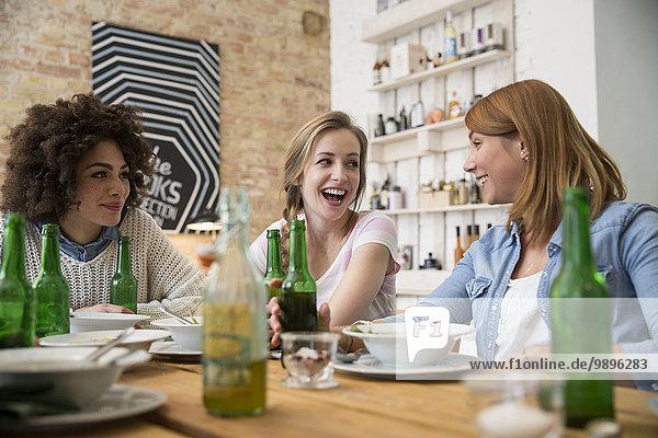 Glückliche Freundinnen am Esstisch mit Bierflaschen
