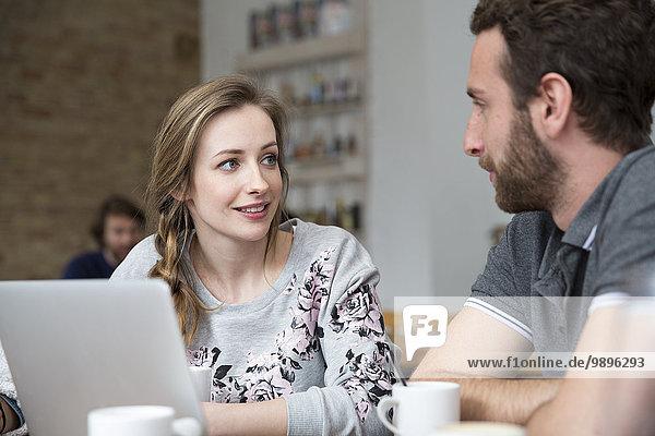 Junger Mann und Frau mit Laptop in einer Cafeteria