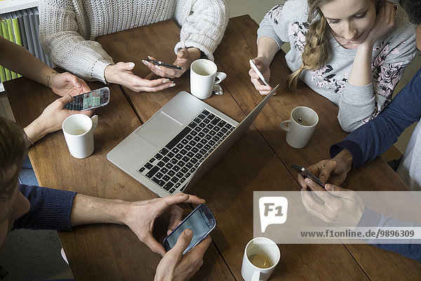 Gruppe von Freunden mit Smartphones in einer Cafeteria