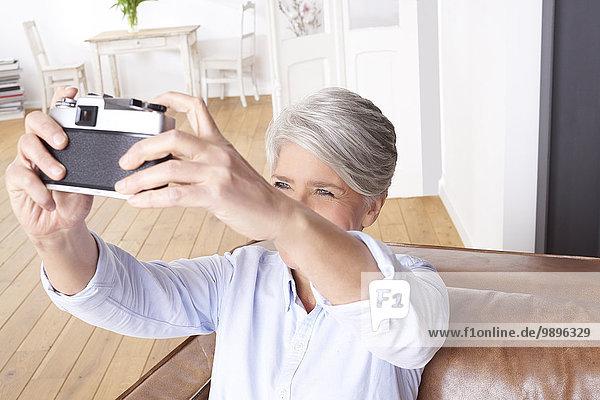 Reife Frau zu Hause mit Selfie