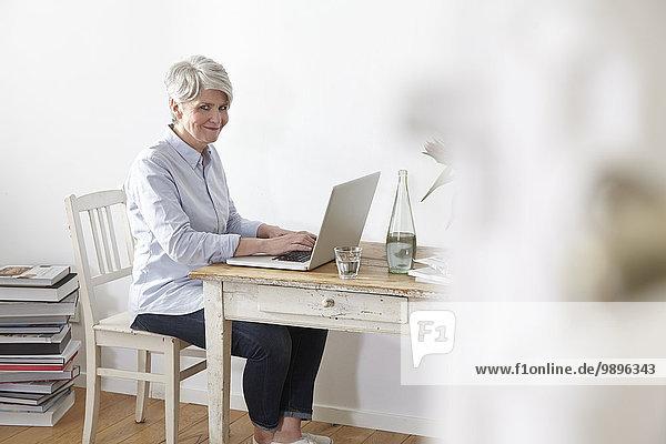 Reife Frau am Tisch sitzend mit Laptop