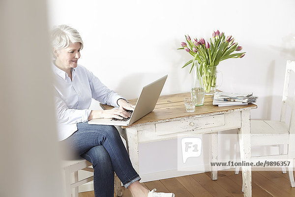 Mature woman sitting at table using laptop