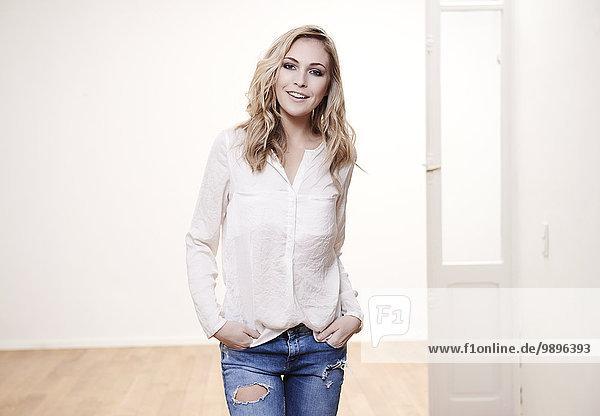 Lächelnde blonde junge Frau