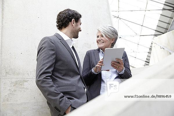 Zwei Geschäftsleute mit digitalem Tablett in moderner Architektur