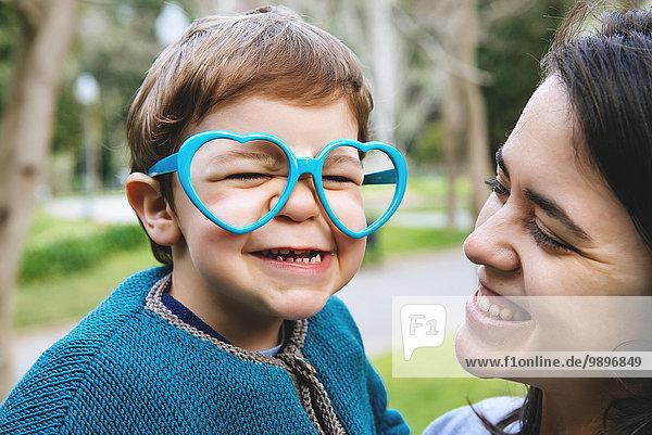 Porträt eines kleinen Jungen  der Gesichter mit herzförmiger Brille macht Porträt eines kleinen Jungen, der Gesichter mit herzförmiger Brille macht