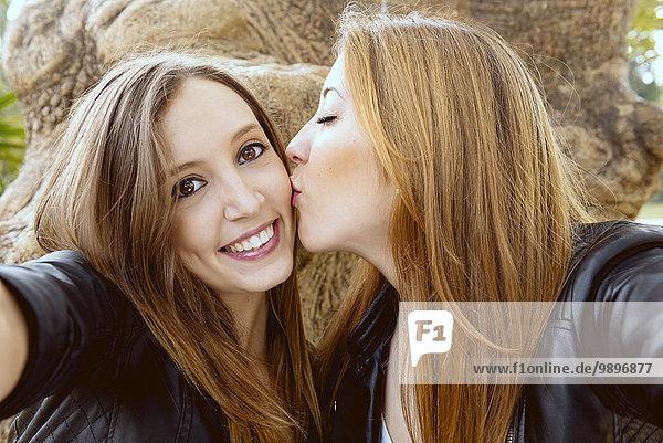 Junge Frau nimmt einen Selfie  während ihre Freundin sie auf die Wange küsst.