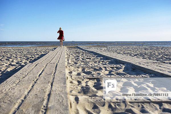 Estland  Paernu  Frau auf Holzsteg am Strand stehend