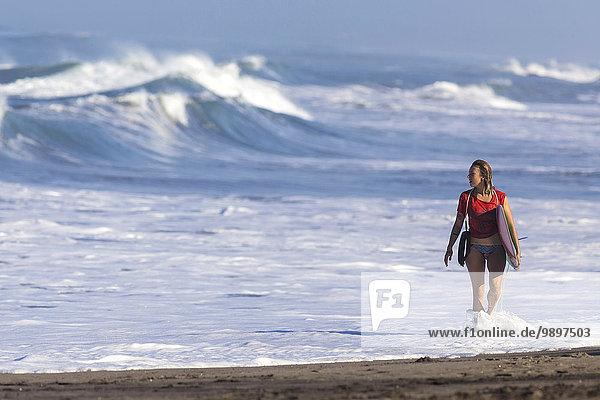 Indonesien  Bali  Frau mit Surfbrett am Meer