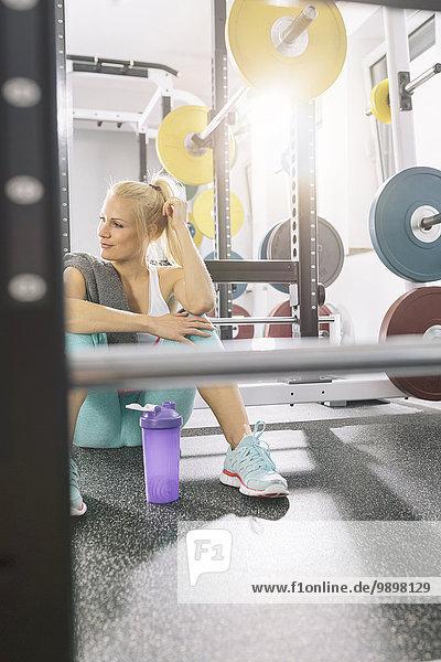 Junge Frau entspannt sich nach dem Training im Fitnessstudio
