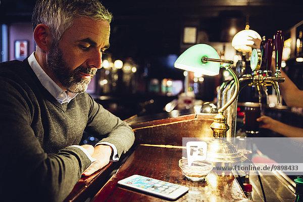 Mann am Tresen einer Kneipe mit Blick auf sein Smartphone