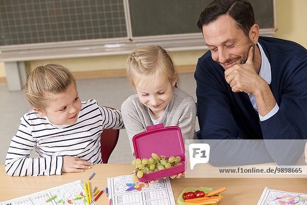 Teacher looking at schoolgirls having healthy breakfast