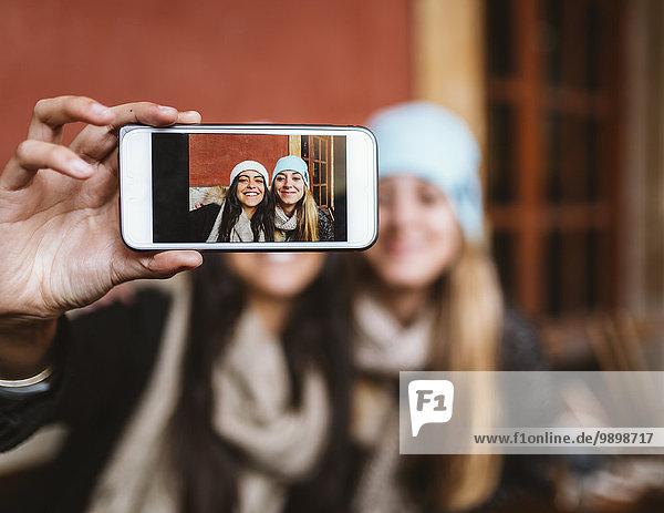 Selfie von zwei Freundinnen auf dem Display des Smartphones