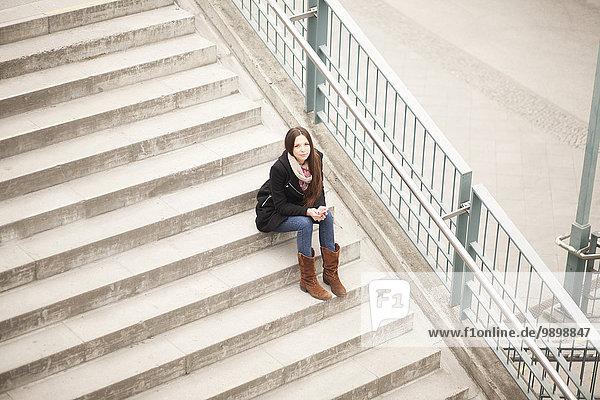 Junge Frau auf der Treppe sitzend