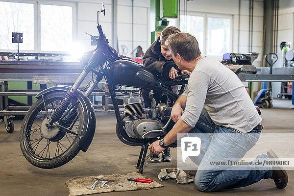 Vater und Sohn pflegen Vintage Moped