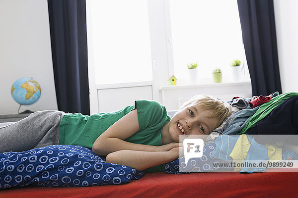 Smiling boy lying on bed