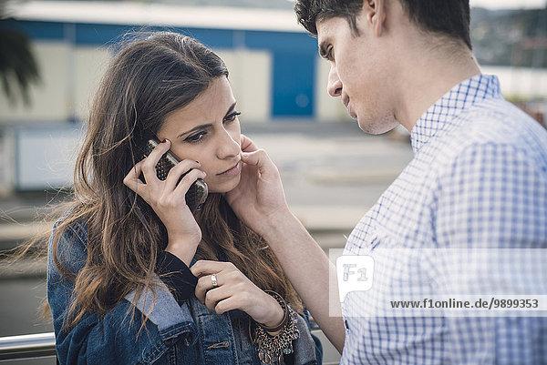 Junge Frau telefoniert  während ihr Freund ihr Gesicht streichelt.
