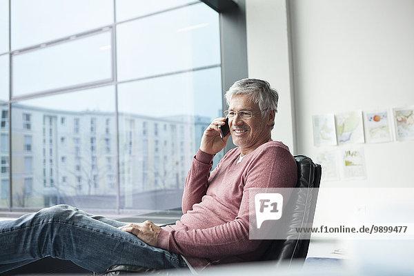 Mann sitzt in einem Ledersessel und telefoniert mit dem Smartphone.