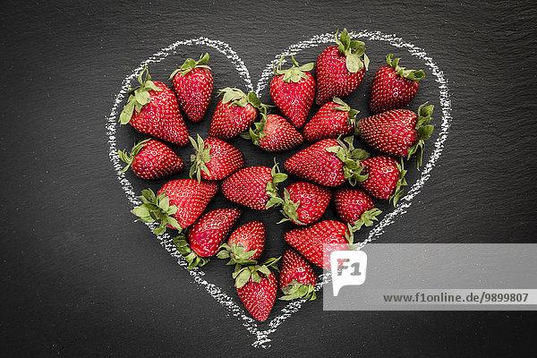 Erdbeeren in Form eines Herzens auf Schiefer