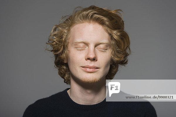 Porträt eines jungen Mannes mit geschlossenen Augen