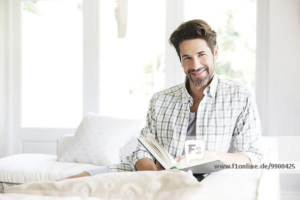 Erwachsener Mann auf Sofa sitzend  Lesebuch