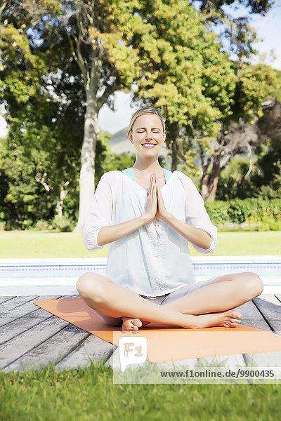 Blonde Frau  die in ihrem Garten Yoga praktiziert.
