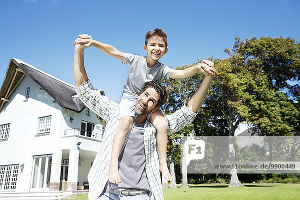 Father carrying son on shoulders  playing in garden