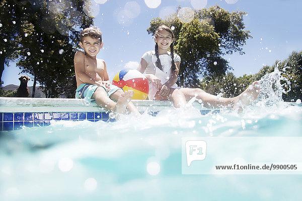 Bruder und Schwester mit Hund am Poolrand sitzend
