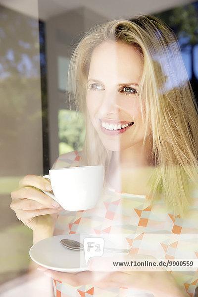 Blonde Frau steht am Fenster und trinkt Kaffee.
