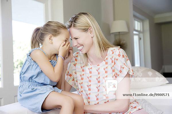 Mutter und Tochter sitzen auf dem Sofa und kichern.