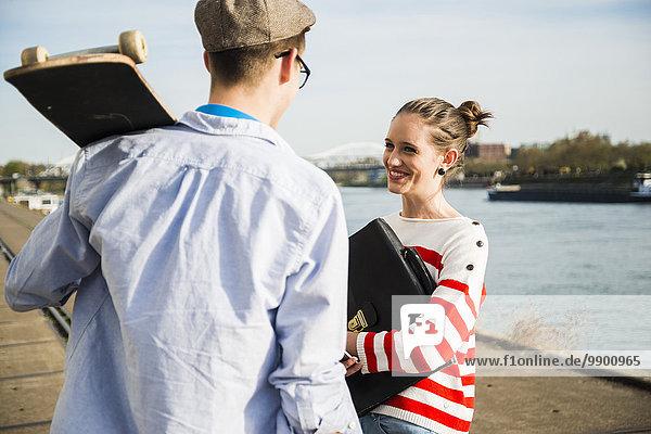Junge Männer und Frauen  die am Flussufer reden.
