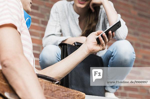 Junger Mann zeigt Handy an Frau