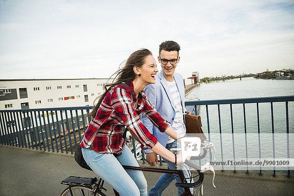 Deutschland  Mannheim  junger Mann und Frau mit Fahrrad auf Brücke