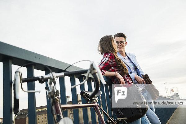 Junger Mann und Frau mit Fahrrad auf Brücke