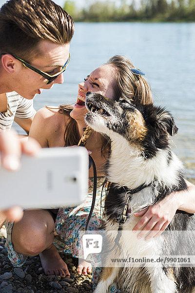 Ein glückliches junges Paar  das sich mit einem Hund am Flussufer vergnügt.
