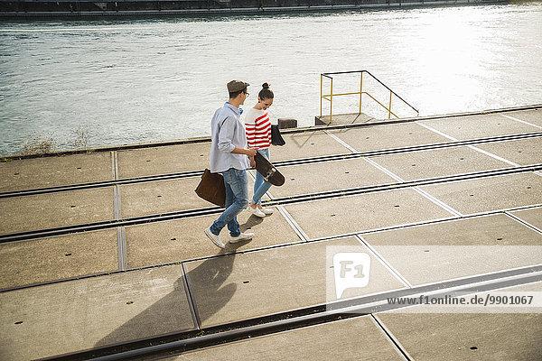 Junger Mann und junge Frau  die am Flussufer spazieren gehen