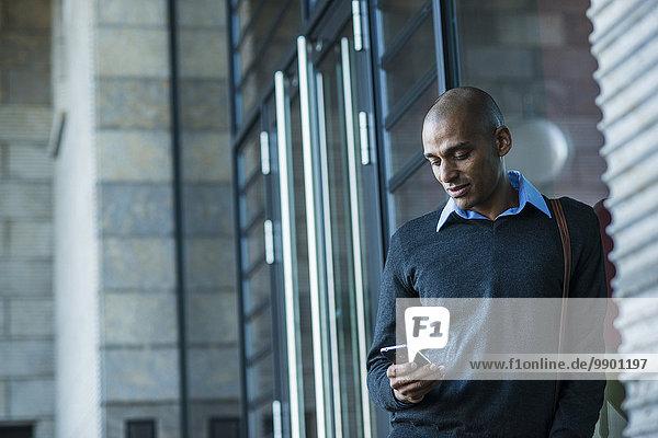 Mann im Freien sucht auf dem Smartphone