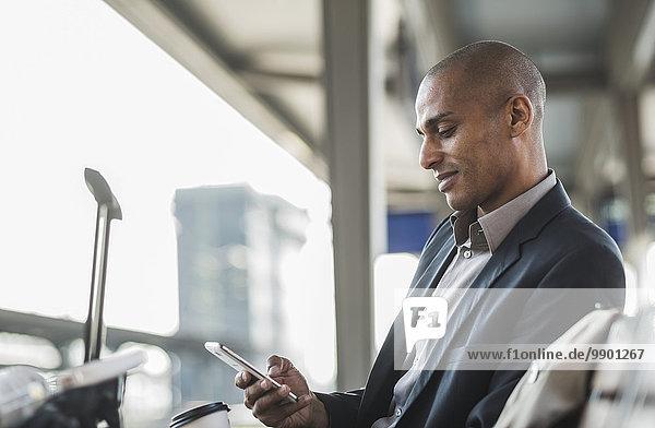 Geschäftsmann am Bahnhof mit Blick auf Smartphone