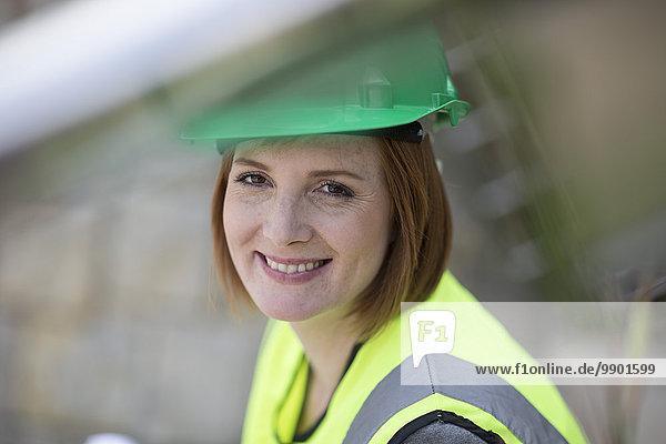 Junge Frau mit Schutzhelm lächelnd auf der Baustelle