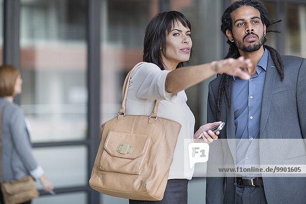 Reisender Geschäftsmann  der die Frau nach dem Weg fragt.