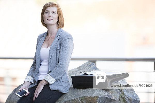 Geschäftsfrau macht eine Pause  sitzt auf einem Felsen und schaut in die Ferne.