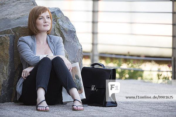 Geschäftsfrau macht eine Pause  sitzt auf dem Boden und schaut in die Ferne.